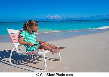 Little girl with laptop on beach during summer vacation -...