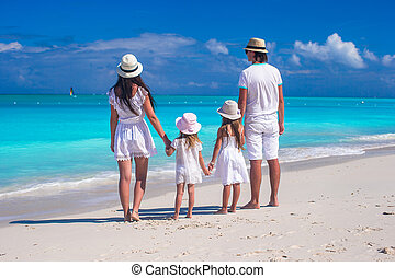 Back view of young family with two kids on caribbean...