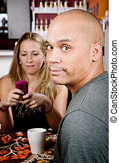 Bored man with woman on cell phone in coffee house