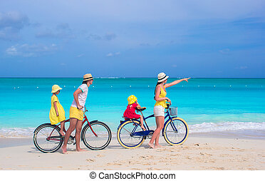 Young family riding bicycles on tropical beach