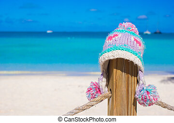 Closeup warm knitted cap on fence at tropical beach -...