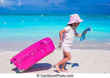 Little adorable girl with big suitcase on tropical vacation...