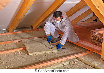 Man laying thermal insulation layer - cutting the panels -...