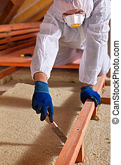 Man laying thermal insulation layer on building - Man...