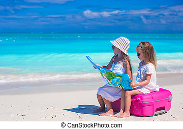 Little girls with big suitcase and map on tropical beach -...