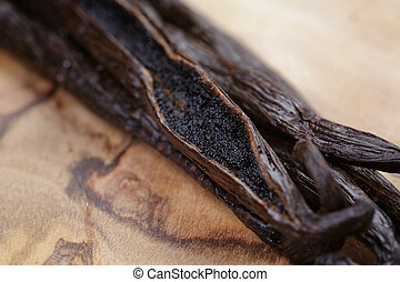 open vanilla pod on olive board, close up photo