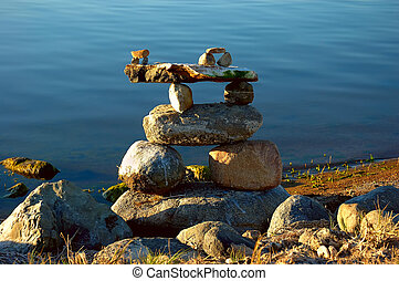 Inukshuk on Calm Water - An Inukshuk is stacked on a calm...