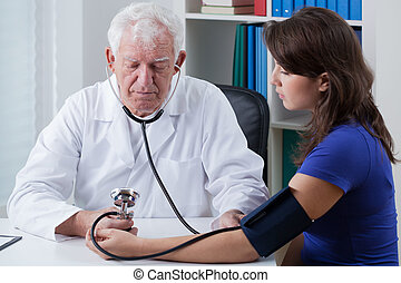 Pressure measurment - Young woman in doctor's office and her...