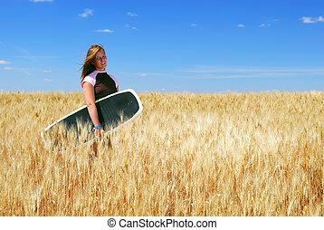 Prairie Boarder Girl in Wheatfield - A pretty teenage girl...