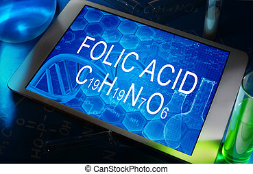 Folic acid - the chemical formula of Folic acid on a tablet...