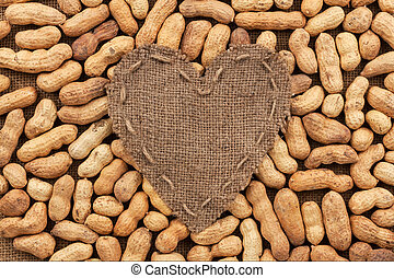 Heart of burlap, lies on a background of peanut, with place...