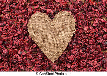 Heart of burlap, lies on a background of dried cranberry,...