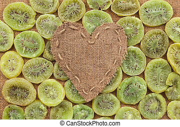 Heart of burlap, lies on a background of dried kiwi, with...