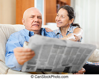 Happy couple of grandparents with newspaper - Portrait of a...