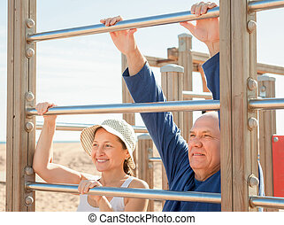 Happy senior couple training on pull-up bar - Happy senior...