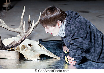 Young man looking at the deer skull - Young man lying down...