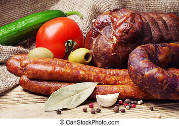 Smoked sausage, meat and vegetables on wooden table