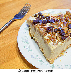 Meal finisher - Big slice of cheesecake with nuts on a plate