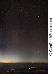 Stars over city lights and mountains panorama