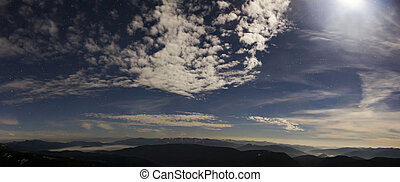 Blue night sky with stars , moving clouds and mountains