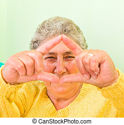 Happy elderly woman showing frame with her fingers
