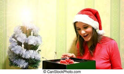 Happy young woman in winter hat open box gift near christmas tree. HD. 1920x1080
