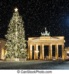 brandenburger tor in december with a christmas tree and...