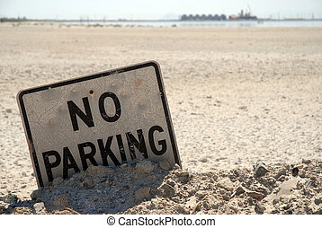 No Parking - A no parking sign half submerged in the desert...