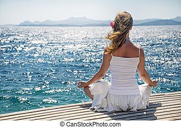 Woman meditating at the sea - serenity and yoga practicing...