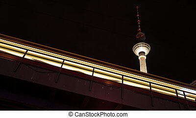 tv tower and train in berlin by night