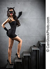 sexy woman in catwoman suit lying on stairs at backyard of...