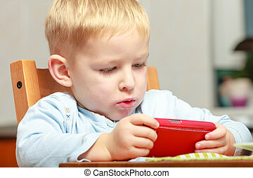 Funny dirty boy child kid taking photo with red mobile phone...