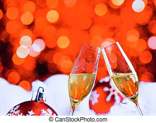champagne flutes with golden bubbles on red christmas lights...