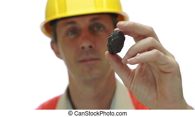 Miner Inspects Carbon Graphite Ore - Short depth of field...