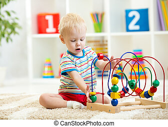 funny child playing with educational toy indoors