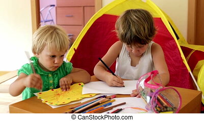 little children sketching at table in home