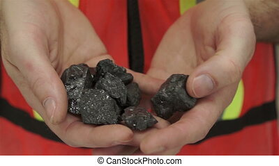 Miner Shows Carbon Graphite Ore - Anonymous male miner in an...