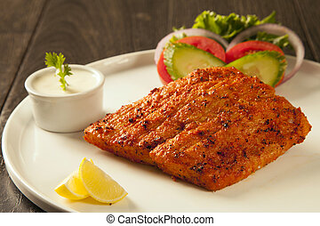 Grilled fish tikka served on a plate with salad and tarter...