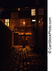 Dark inner city cobblestoned back alley with streetlight at...