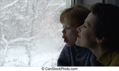Blizzard Outside the Window - Mother with young son looking...
