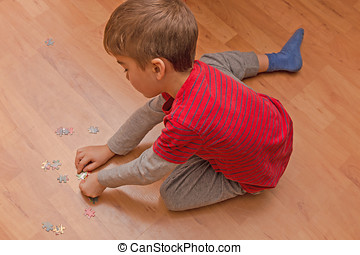 pensive child collects puzzles - European boy playing with...