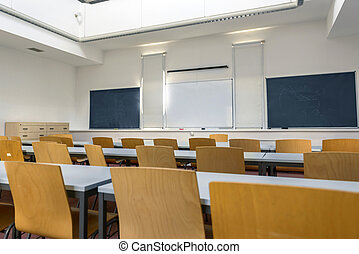 Empty classroom with chairs, desks and chalkboard.