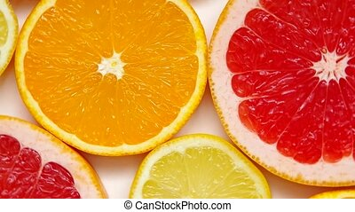 Sliced grapefruit, orange and lemon rotates on a plate