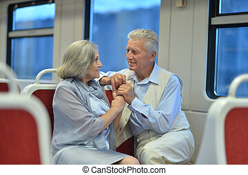 Senior couple in train looking at window
