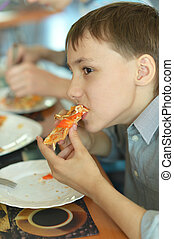 boy eating pizza  - Portrait of  boy eating pizza in cafe