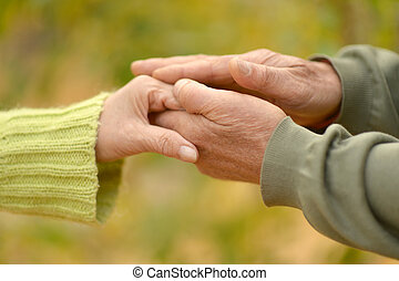 couple holding hands - Elderly couple holding hands in...