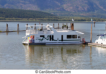 Houseboat docked at pier in Salmon River, British Columbia,...