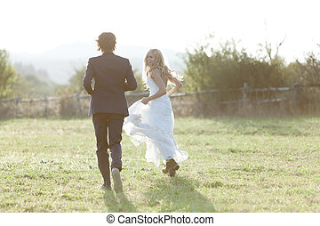 Summer love - Married couple running in a field, having fun...