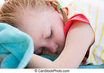 Adorable little girl at beach sleeping on towel tired after...