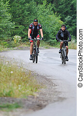 friendshiop outdoor on mountain bike - two friends have fun...